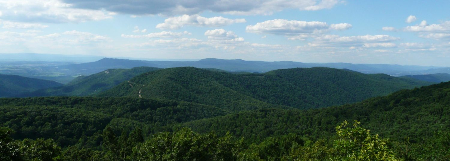 A wide vista view of the Appalachian mountains, covered in forest, on a sunny day