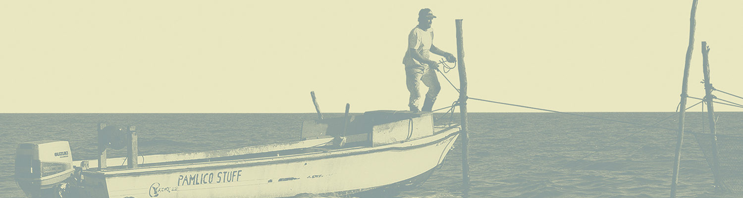 A man stands on the bow of a small motor boat in Pamlico Sound, tying it to a wooden post in the water.